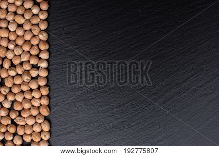 Chickpeas Lies On A Black Stone Board, Space For Text, Black Background