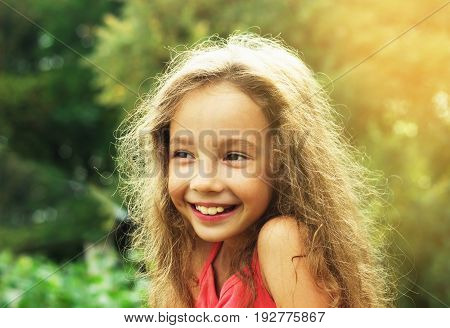 Beauty Girl Outdoors enjoying nature at sunset. Beautiful Teenage girl with long hair smiling. Happy kid. Toned in warm colors