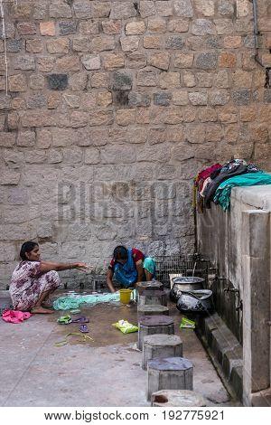 Mysore India - October 26 2013: Public wash area for faithful before entering Jamia Masjid mosque on Sriranagapatna Island. Stone octagonal seats. In photo two women do laundry.