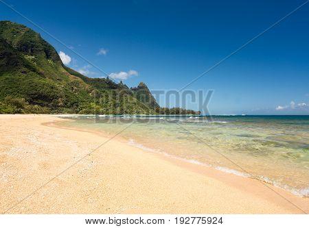 View down the sand at Tunnels Beach in summer on Hawaiian island of Kauai on North Shore