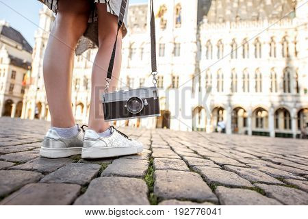 Woman standing with photo camera on the Grand place with city hall on the background in the old town of Brussels, Belgium
