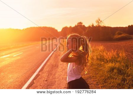 Beauty Girl Outdoors enjoying road trip at sunset. Beautiful Teenage girl with long hair Thinking. Happy kid. Toned in warm colors