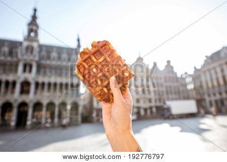 Holding a traditional belgian waffle on the central square background with city hall in Brussels. Belgian food concept