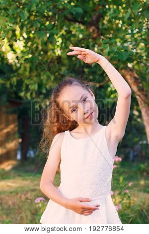 Cute little girl dreams of becoming a ballerina. Child girl in white dress dancing outside. Beautiful Preteen Girl is studying ballet.
