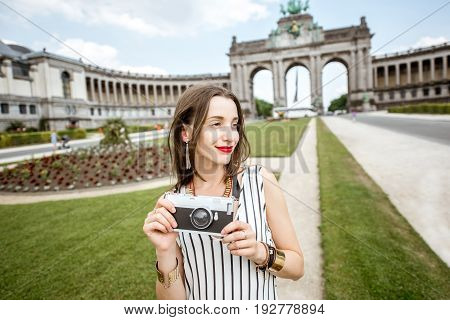 Young female traveler standing with photo camera on the famous Triumphal arch background in Brussels
