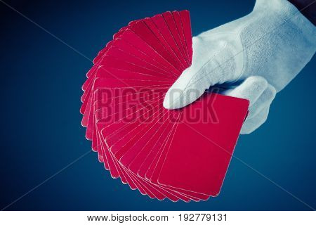 Playing cards game poker hand with white glove on dark blue background. Casino games collection