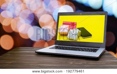 Laptop computer with mini supermarket shopping cart mini colorful gift box and smart phone on yellow in screen with blurred night light bokeh background holiday sale and shopping online concept