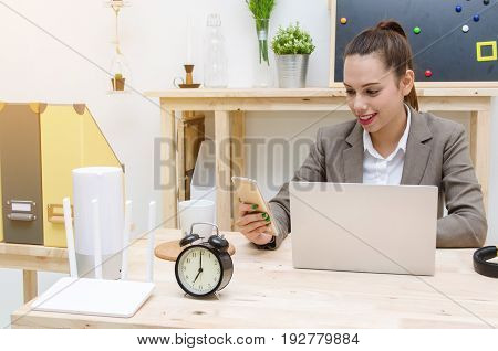 asian young business woman beautiful smile using smartphone on wood table with alarm clock headphone laptop notebook computer wireless router document folder selective focussunlight effect