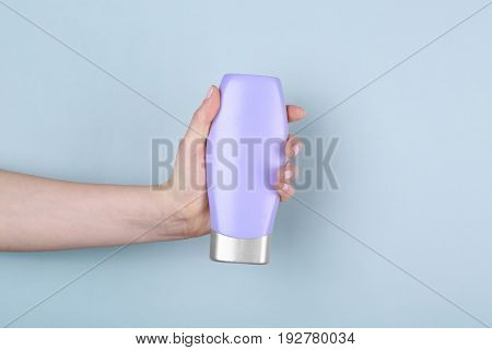 Female hand with bottle of cosmetic product for shower on color background