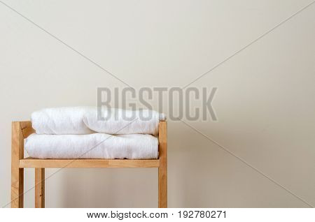 white towels on wooden shelves on white wall in bathroom selective focus copy space
