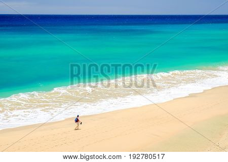 Aerial view on the beach with amazing water colors of the Atlantic Ocean in Mal Nombre and a person walking along it on the Canary Island Fuerteventura in Spain closed to Morro Jable and Sotavento beaches.