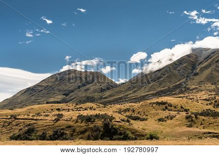 Middle Earth New Zealand - March 14 2017: Mountain range at Middle Earth under blue cloudy sky. High desert scenery with sparse brown vegetation. Shale pebble flow off top.
