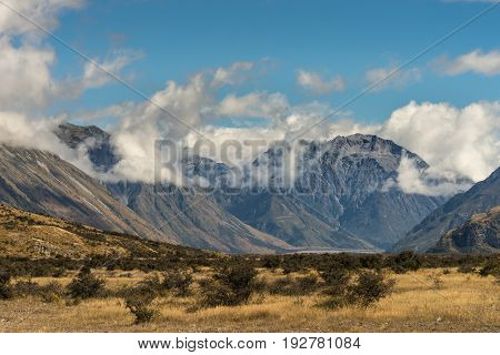Middle Earth New Zealand - March 14 2017: High mountain range around Rock of Middle Earth under blue sky with white clouds. Set in a high desert mountainous scenery.