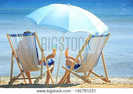 Young couple with cocktails sitting on beach chairs at sea shore. Vacation concept
