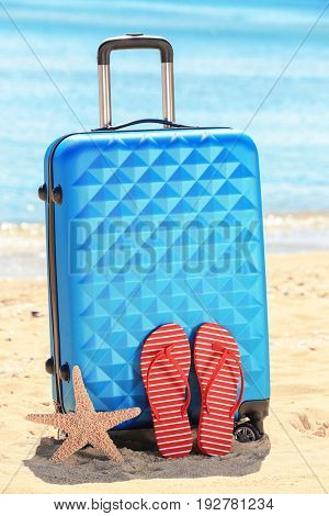 Packed suitcase, flip-flops and starfish at sea shore. Vacation concept