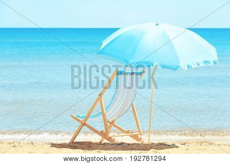 Beach chair and umbrella at sea shore. Vacation concept