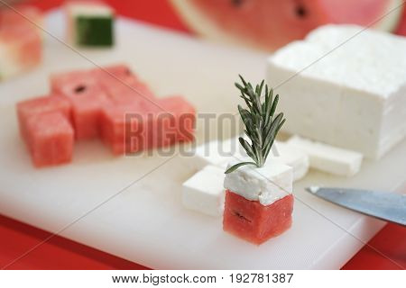 watermelon and feta cheese cubes with rosemary. authentic greek cuisine with selective focus.
