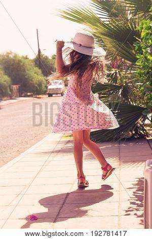 Beautiful Girl outdoors enjoying nature. Beautiful Teenage girl dancing on summer street. Toned in warm colors. Soft focus