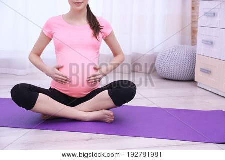 Beautiful pregnant woman doing exercise at home