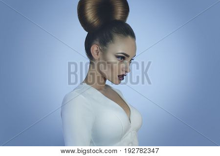 Glamour young lady with creative hairstyle and make up in studio