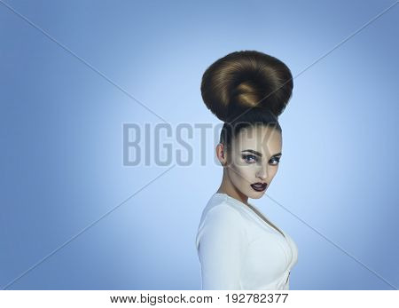 young glamour lady with creative high hairstyle and beautiful make up looking away in studio