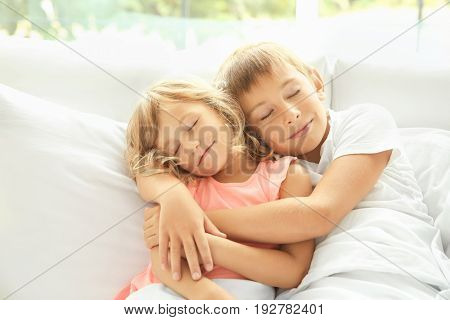 Portrait of little boy and girl sleeping in bed