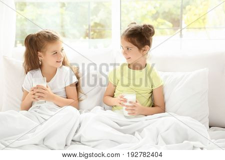 Portrait of two little girls in bed with glasses of milk