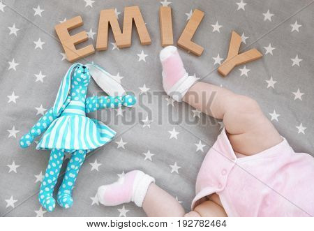 Legs of cute baby, toy and word EMILY composed of wooden letters on bed. Choosing name concept