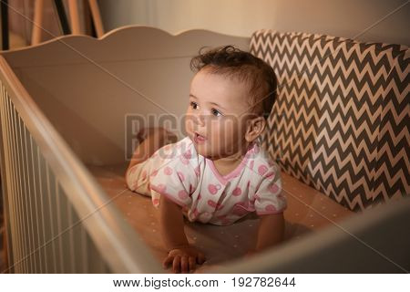 Cute little baby lying in cradle at home. Sleep disorders concept