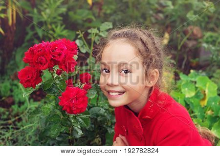 Portrait of Little Girl in the Summer time. Beautiful Girl smiling in rose Garden