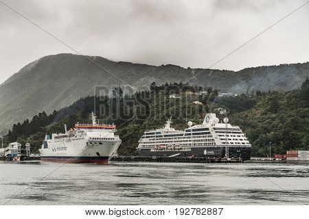 Picton New Zealand - March 12 2017: Interislander ferry leaves Picton port under heavy rainy skies. Azamara Cruise ship in harbor. Green forest on mountains in back.