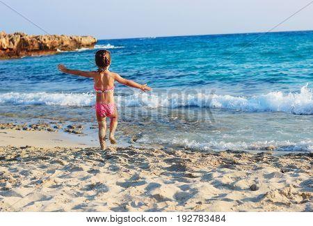 Happy Cute Little Girl running on the coast of warm Sea at Summer Sunset