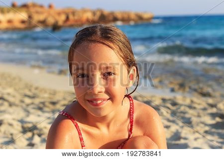 Happy Cute preteen Girl sitting and smiling on the coast of warm Sea at Summer Sunset
