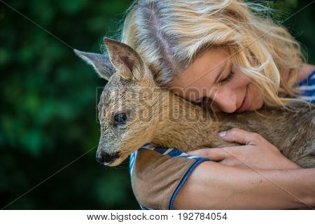 Animal care concept, Young woman taking care of young deer fawn