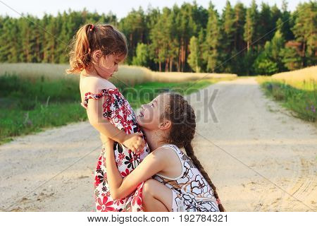 Two beautiful little girls smiling and playing at the field in warm summer day