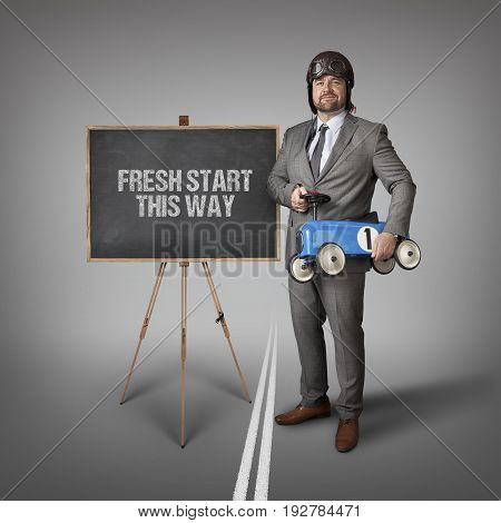Fresh start this way text on blackboard with businessman and toy car