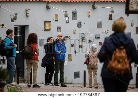 Vilnius Lithuania - June 25 2017: Tourists walk on Literatu street in Vilnius attractive place of old town. Artworks mounted on the walls of this street dedicated to the literature workers: writers poets translators.