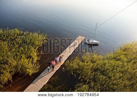 Zarasai Lithuania - July 25 2015: Participants of a wedding take photographs on the pier in Zarasas lake.