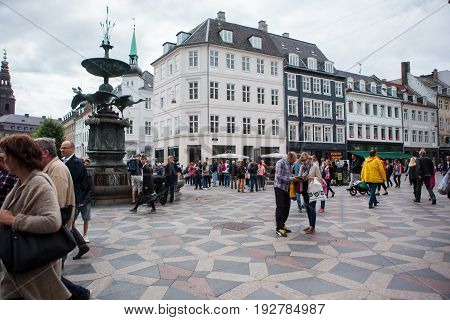 Copenhagen Denmark - July 29 2015: Tourists and locals walk in Amagertorv the most central square in central Copenhagen Denmark.