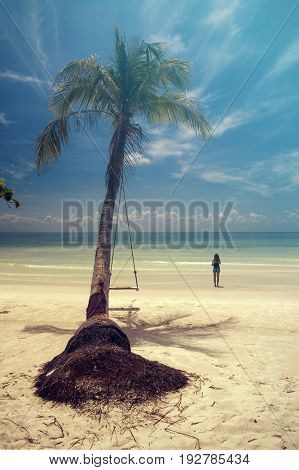 Girl on a tropical beach with swing on a palm tree, white sand and blue sky. Vintage effect.
