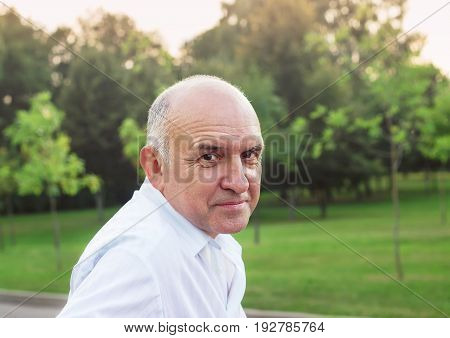 Portrait of friendly smiling senior man outdoors