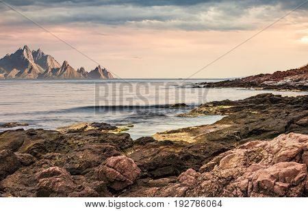 Seascape With Rocky Coast And Mountain Ridge With High Peaks