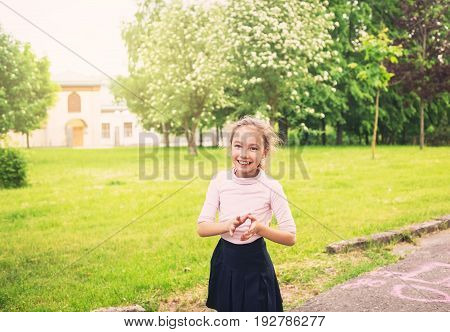 Happy preteen girl running on meadow in summer day at sunset