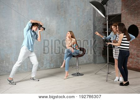 Group of students taking photo of model during photography classes