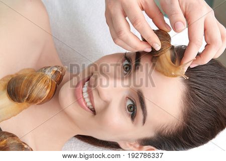 Young woman undergoing treatment with giant Achatina snails in beauty salon, closeup