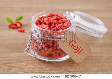 Goji berries in a glass jar and label with text goji on wooden background