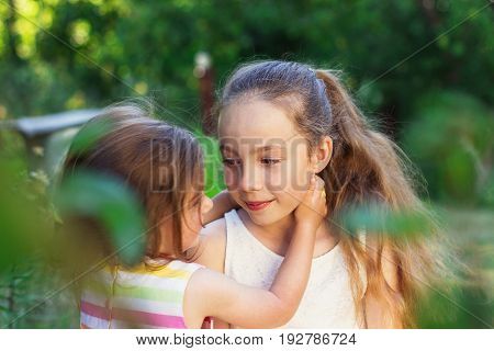 Two cute little girls hugging and playing in the park at the day time