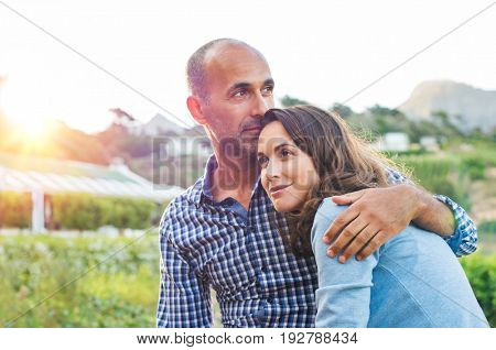 Loving man and happy woman in a spring blooming park. Happy mature couple in love embracing outdoor. Hispanic boyfriend embracing her brunette girlfriend during sunset in a summer day.