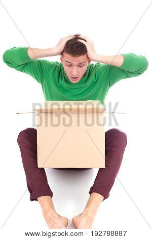 Sad, tired and surprised deliveryman hardly carries the parcel, isolated, white background