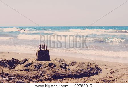 Holiday concept with sandcastle on the seaside. Toned